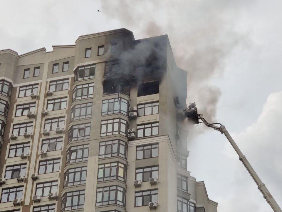 Людина стоїть над прірвою, стовпи диму видно на кілометри: у Києві палає багатоповерхівка, є загиблий (фото, відео)
